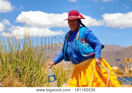 UROS FLOATING ISLANDS PERU - SEPTEMBER 19: Indigenous woman in traditional clothing on the Uros Floating Islands in Peru on September 19 2014