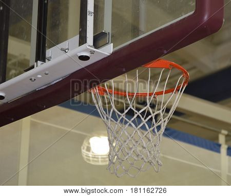 from behind shot of basketball backboard in gymnasium