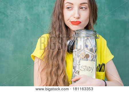 Thoughtful and sad woman in yellow t-shirt holding a bottle with money savings for study