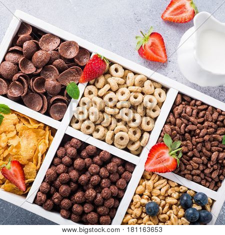 Variety of cold quick breakfast cereals with berries in white wooden box, healthy eating for kids, overhead shot