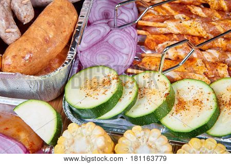 Marinated meat sausages and vegetables prepared for grilling