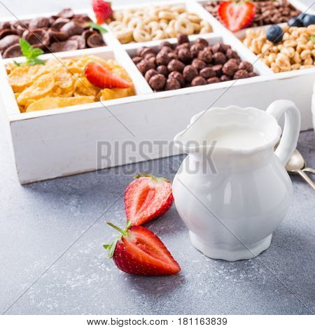 Milk jug and quick cereals with berries in white wooden box, healthy breakfast concept, selective focus, copy space.