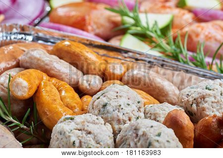 Marinated meat, sausages and vegetables prepared for grilling