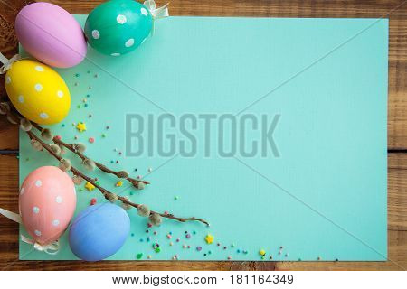 Easter background. Multicolored decorated easter eggs multi-colored powder and willow twigs on a turquoise background on a wooden table. Free space