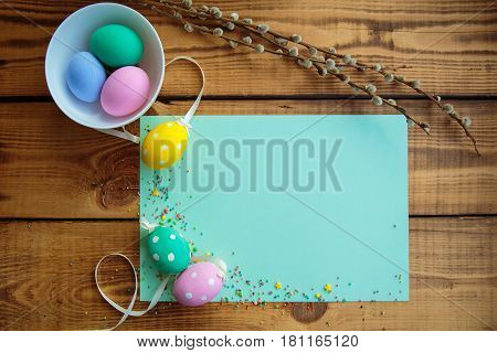 Easter background. Multicolored decorated easter eggs in a white plate multi-colored powder and willow twigs on a turquoise background on a wooden table. Free space