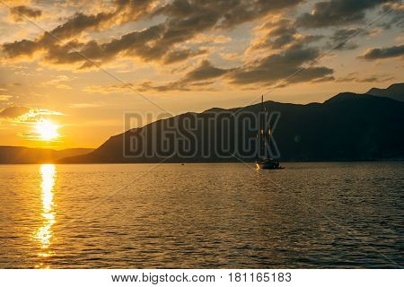 Yacht in the sea at sunset. Silhouette of a yacht on the background of the setting sun on the horizon