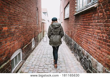 Lonely female person walking in the street photographed from behind