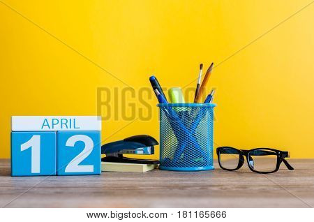 April 12th. Day 12 of month, calendar on business office table, workplace with yellow background. Spring time.