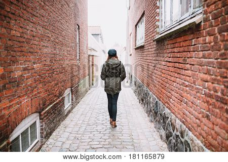 Woman walking in the street photographed from behind
