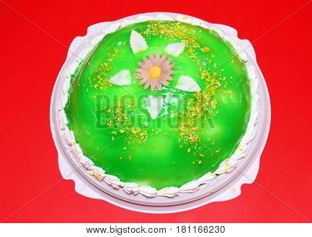 sweet cake with green jelly on red background
