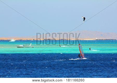 surfing - windsurfers and kitesurfer on blue sea surface