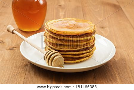 Vegan butternut squash puree pancakes on white plate with honey. Healthy gluten free breakfast on wooden table