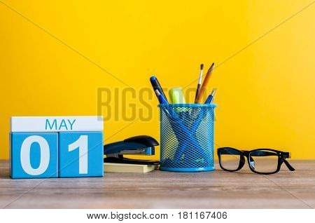 May 1st. Day 1 of month, calendar on business office table, workplace at yellow background. Spring time.
