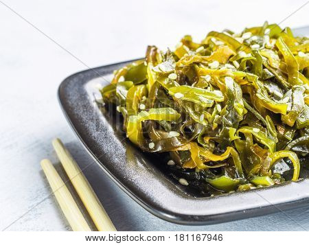 Close up view of kelp seaweed salad with sesame seeds in black plate on gray concrete background. Copy space.