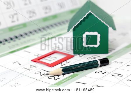 Pencil on the background of a cardboard green house and a calendar with a bookmark on the date. Business Details