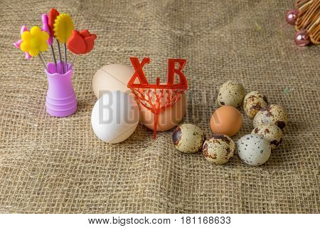 three chicken eggs and quail eggs Guinea fowl egg are lying together on a wooden table covered with burlap