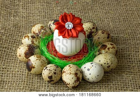 quail eggs and chicken egg with red bow are in a circle around the plastic blue bowl of red salt on a wooden table with natural burlap