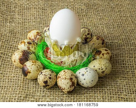 quail eggs and chicken egg is one with the crown are in a circle around the plastic blue bowl of red salt on a wooden table with natural burlap