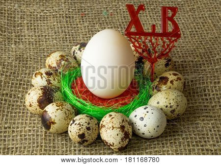 quail eggs and chicken egg are in a circle around the plastic blue bowl of red salt on a wooden table with natural burlap