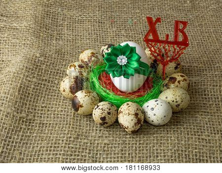 quail eggs and chicken egg with green bow are in a circle around  of red salt on a wooden table with natural burlap