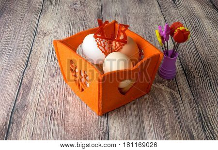 chicken eggs for Easter holiday coloring in an orange textured soft box on a wooden table