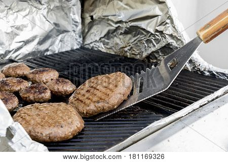 Juicy cutlets on the grill. Large juicy cutlet on the grill is turned over. Tool for grilling.