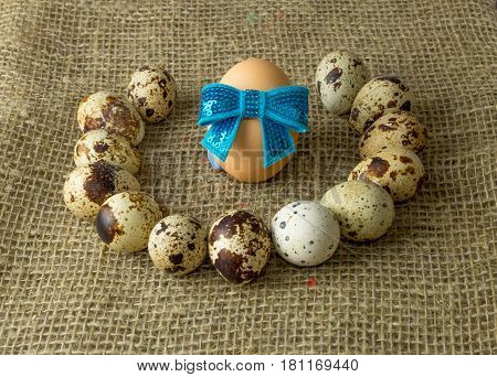 quail eggs and chicken egg with a blue bow around lying on a wooden table with natural burlap