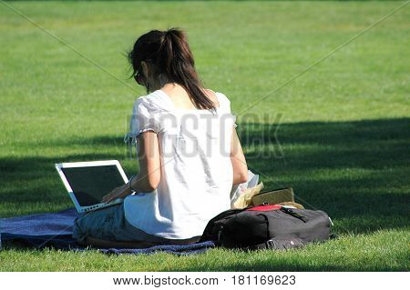 Female student working on her computer at a public park outdoors.