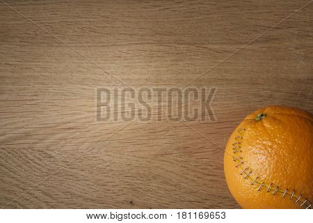 Orange With Stainless Steel Sutures On A Wodden Board