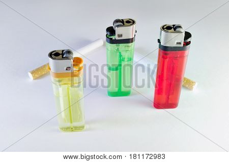 multicolored disposable flint gas lighters and two cigarettes with filter