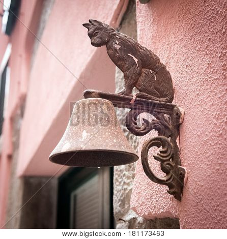 Metal figure of cat as decoration of bell carried on a wall
