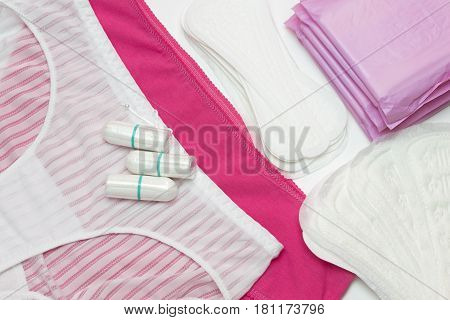 Pink and white pants. Menstruation sanitary pads and cotton tampons for woman hygiene protection. Soft and tender protection for woman critical days gynecological menstruation cycle