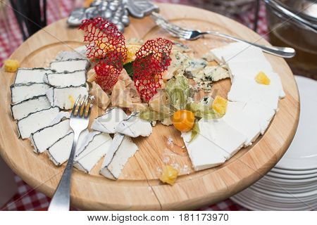 round wooden plate with different kinds of cheese, grapes, walnuts and honey. Top view. Brunch at an expensive restaurant