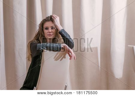 Beautiful young blonde woman sitting astride a chair, in pensive state of mind looking at camera