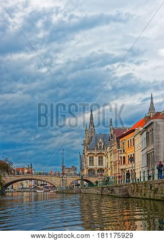 Belgium, Ghent - May 8, 2012: Old city center Graslei with St Michael Bridge over Leie River and Former Post Office in Ghent in East Flanders Belgium. People on the background