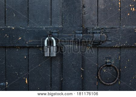 Lock with a latch on an old metal door in black