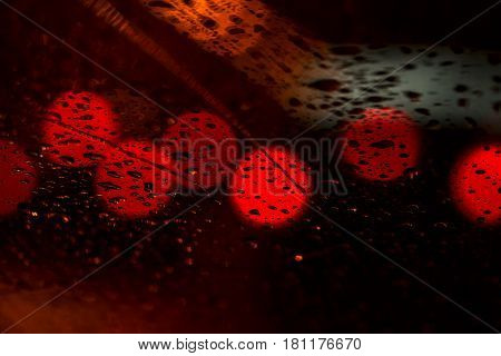 Night lights of urban traffic seen through the windshield in rainy weather. Abstract background. Concept of night city life and cars