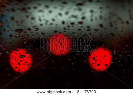 Night lights of urban traffic seen through the windshield in rainy weather. Concept life of a modern city, urban traffic, night car driving. Abstract background.