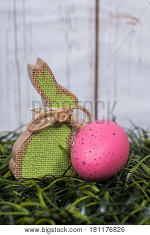Wooden easter bunny decorated in burlap with pink egg