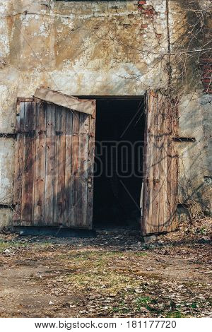 The wooden gate collapsed in the old abandoned factory warehouse, vertical image