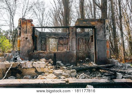 Ruined and burnt house, scattered bricks, can be used as demolition, earthquake, bomb, terrorist attack or natural disaster concept