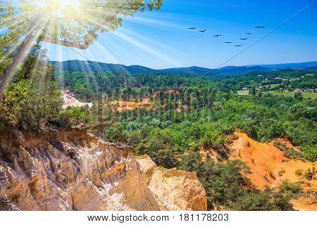 Unique red and orange hills in the province of Languedoc - Roussillon. The sun strengthens the color of ocher. The concept of ecological tourism