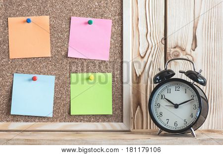 Time Management Concept With Alarm Clock On Wooden Shelf And Reminder Color Papers On Cork Board