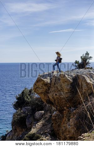 Blond woman photographer enjoying seaview and standing on high rock cliff portrait layout