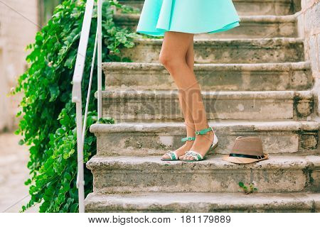 Female feet in sandals. On the stone steps. A girl in a blue sarafan.