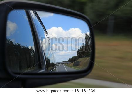 Road reflecting in the sideview mirror of a car