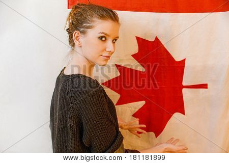Young immigrant girl in black pullover looking back posing in front of Canada flag vintage color image
