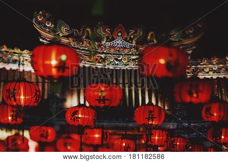 True tilt shift view of multiple traditional Chinese New Year red lanterns with black hieroglyphs on them ceramic ornament of two dragons in blurred night background
