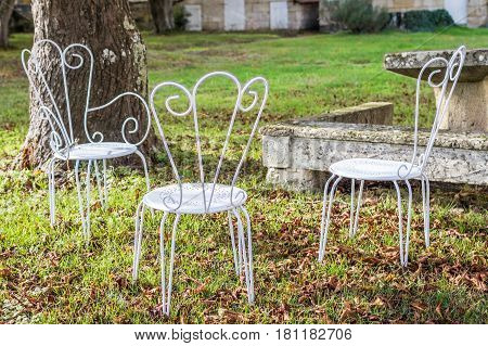 Decorative vintage metal white chairs furniture in a garden in France
