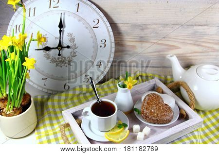 Breakfast in bed with a Cup of tea with lemon,gingerbread, alarm clock and daffodils